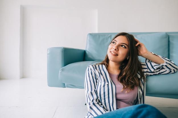Jonge rustige vrouw ontspannen, zittend op de vloer in de buurt van de bank in de moderne woonkamer