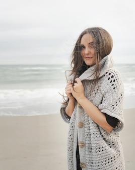 Jonge rustige vrouw portret tegen een zee, wniter huidverzorging concept
