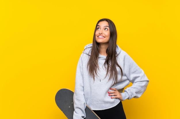 Jonge schaatservrouw die op geel wordt geïsoleerd dat omhoog terwijl het glimlachen kijkt
