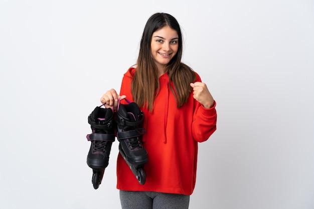 Jonge schaatservrouw die op wit wordt geïsoleerd dat een overwinning in winnaarpositie viert