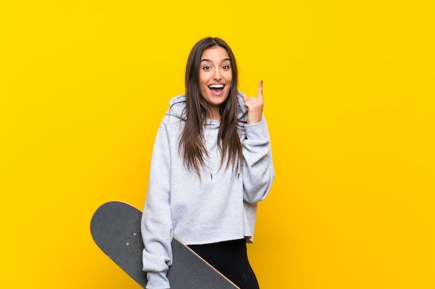 Jonge schaatservrouw over geïsoleerde gele muur die een groot idee benadrukken