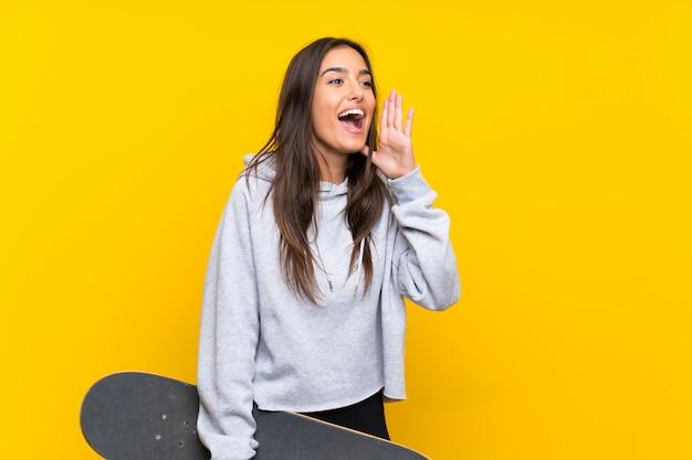 Jonge schaatservrouw over geïsoleerde gele muur die met wijd open mond schreeuwen