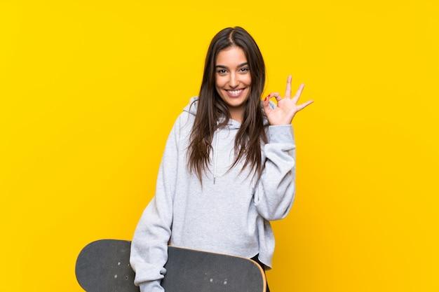 Jonge schaatservrouw over geïsoleerde gele muur die ok teken met vingers tonen