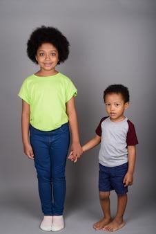 Jonge schattige afrikaanse broer en zus hand in hand