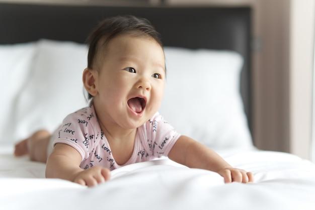 Jonge schattige aziatische baby kruipen op bed in de slaapkamer. de baby lacht en kijkt recht.