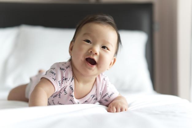 Jonge schattige aziatische baby kruipen op bed in de slaapkamer. de baby lacht.