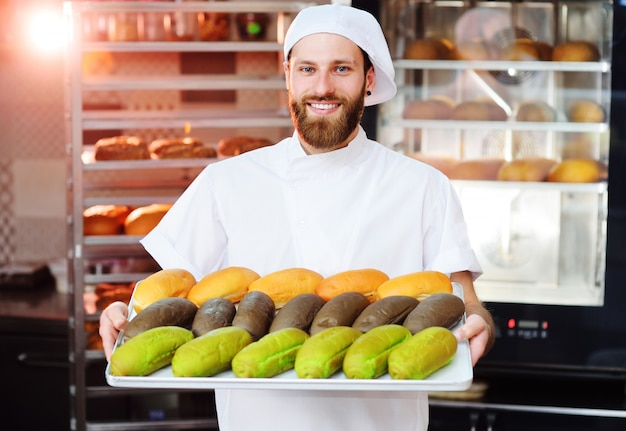 Jonge schattige baker in witte uniform houden een dienblad met gekleurde broodjes voor hotdog op het oppervlak van bakkerij of broodfabriek