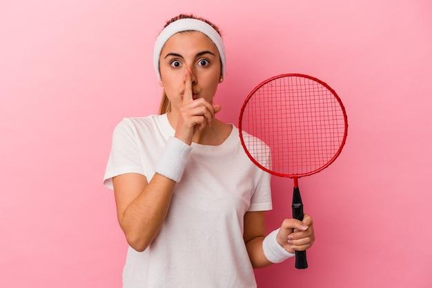 Jonge schattige blonde blanke vrouw die een badmintonracket houdt dat op roze achtergrond wordt geïsoleerd die een geheim houdt of om stilte vraagt.