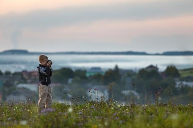 Jonge schattige blonde kindjongen met fotocamera die zich op grasrijke heuvelbovenkant bevinden op de lente of de zomerdag.