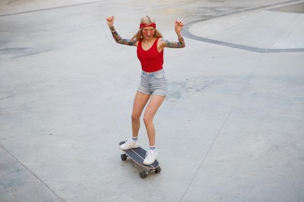 Jonge schattige blonde met getatoeëerde armen in een rood t-shirt en spijkerbroek met een gebreide bandana op haar hoofd, in rode bril, met handen omhoog, genietend van de dag en longboarden in skatepark.