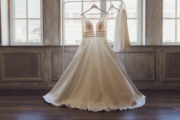 Jonge schattige brunette bruid kijkt naar haar trouwjurk.