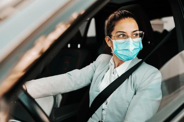 Jonge schattige brunette smart casual gekleed met gezichtsmasker bij het besturen van haar auto tijdens de uitbraak van het coronavirus.