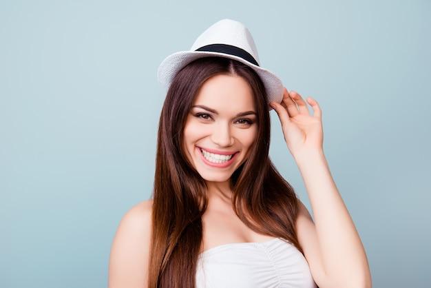 Jonge schattige brunette toothy dame in zomer outfit en trendy zomer toeristische hoed staat op een lichtblauwe ruimte, tot vaststelling van haar pet. ze is zo stijlvol en aantrekkelijk