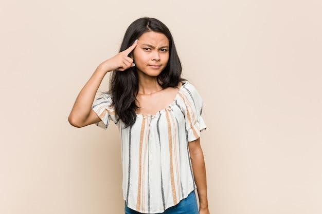 Jonge schattige chinese tiener jonge blonde vrouw draagt een jas tegen een roze muur met een teleurstelling gebaar met wijsvinger.