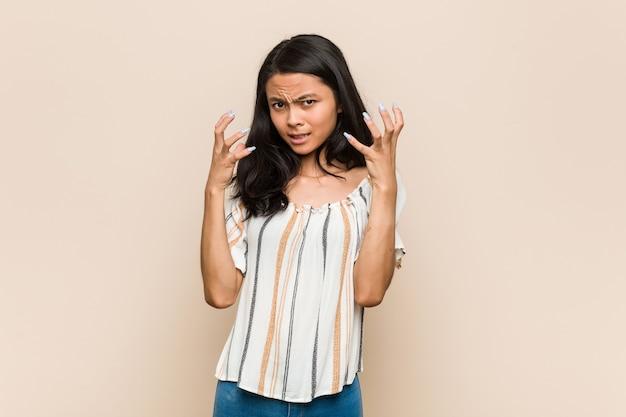 Jonge schattige chinese tiener jonge blonde vrouw, gekleed in een jas tegen een roze muur boos schreeuwen met gespannen handen.