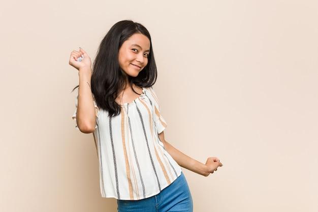 Jonge schattige chinese tiener jonge blonde vrouw, gekleed in een jas tegen een roze muur dansen en plezier maken.