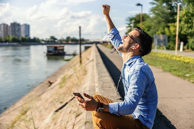 Jonge schattige dolgelukkig hipster aan de rivier zitten en genieten van de muziek op een mooie zonnige dag.