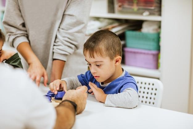 Jonge schattige jongen met het syndroom van down in blauw shirt zit aan wit bureau met andere kinderen en studeren.