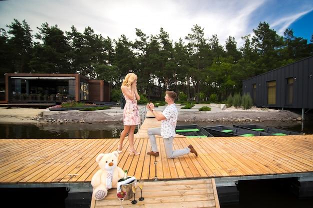 Jonge schattige kerel doet een aanzoek naar zijn geliefde meisje, staande op zijn knie op een houten pier. romantiek en liefde op een houten pier