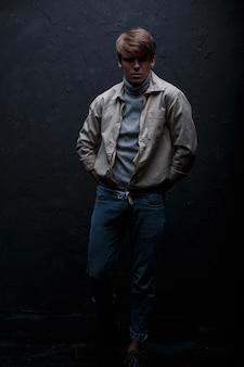 Jonge schattige knappe man met een modieus kapsel in een witte stijlvolle jas in vintage jeans in grijze trui staat in een donkere studio op een grijze achtergrond. stijlvol, geweldig jongensmodel