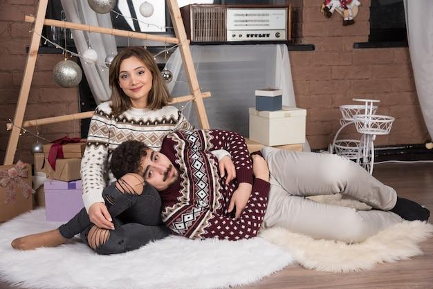 Jonge schattige lachende paar zittend op de vloer en poseren.