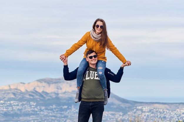 Jonge schattige meisje zittend op de schouders van haar vriendje