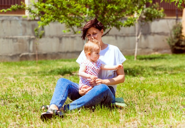 Jonge schattige moeder zit op het gras in de tuin, houdt haar dochter vast en zegt iets tegen haar. schattig meisje in een zomerjurk in de armen van haar moeder. zomer familie tijd en frisse lucht concept
