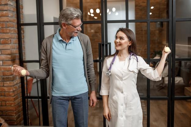 Jonge schattige verpleegster die fysiotherapiebehandeling in huis doet met senior man met halters.