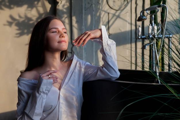 Jonge schattige vrolijke vrouw in wit overhemd wegkijken in vintage badkamer bij badkuip met schaduw van gebladerte. reclameconcept van gezonde levensstijl en zelfzorg. ruimte kopiëren voor site of spa