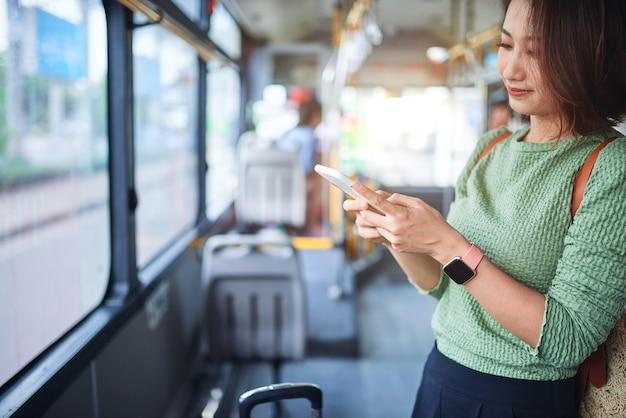 Jonge schattige vrolijke vrouw staat in de bus met behulp van de telefoon en glimlacht.