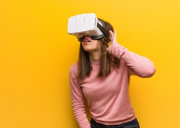 Jonge schattige vrouw draagt een virtual reality-bril probeert te luisteren naar een roddel