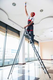 Jonge schilder die het plafond in bouwconcept schildert