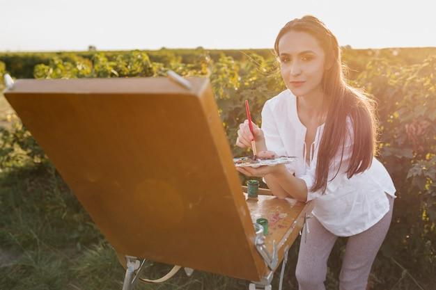 Jonge schilder in de aard die camera bekijkt