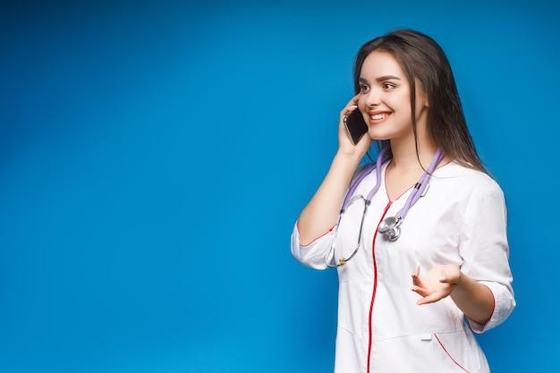 Jonge schitterende arts die telefonisch met patiënt op blauw spreekt.