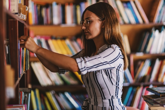 Jonge schitterende vrouwelijke student die zich naast boekenplanken bevindt en naar het boek voor examens zoekt.