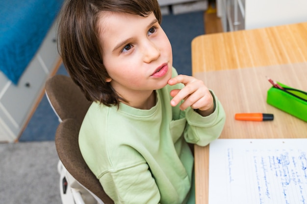 Jonge school jongen zijn huiswerk aan de tafel thuis zitten. geconcentreerd kind denkt met belangstelling na over een taak. thuisonderwijs.
