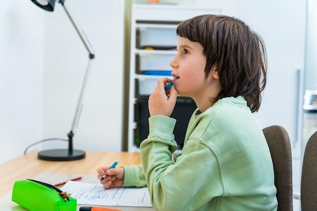 Jonge school jongen zijn huiswerk aan de tafel thuis zitten. geconcentreerd kind denkt met plezier na over een taak. thuisonderwijs.
