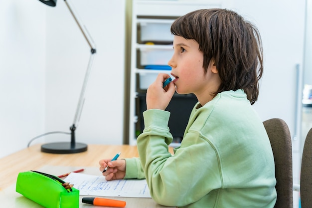 Jonge school jongen zijn huiswerk aan het bureau thuis zitten. geconcentreerd kind denkt met belangstelling na over een taak. thuisonderwijs.