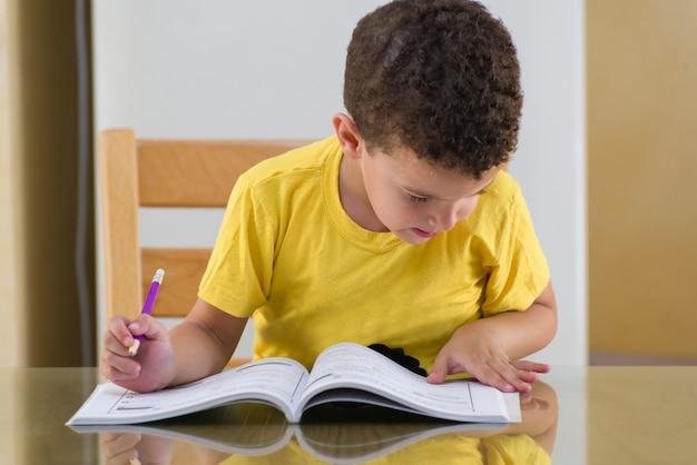 Jonge schooljongen die hard studeert