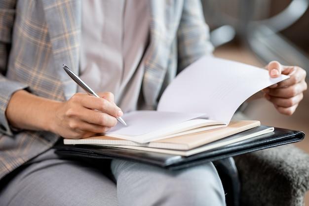 Jonge schoolleraar met pen die fouten corrigeert of teken in voorbeeldenboek van student of scholier zet