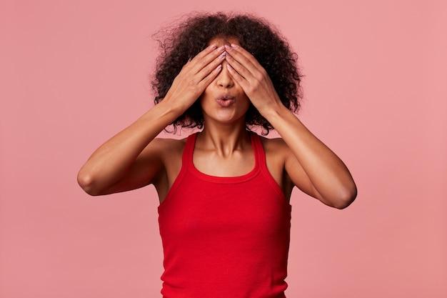 Jonge schoonheid african american vrouw met donker krullend haar, gekleed in een rode t-shirt. bedekt haar ogen met handen en maakt zich klaar om te kussen, geïsoleerd.