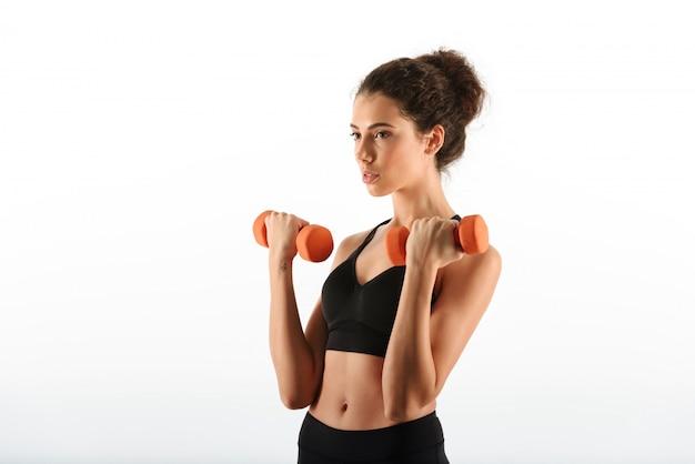 Jonge schoonheid fitness vrouw doet oefening met halters