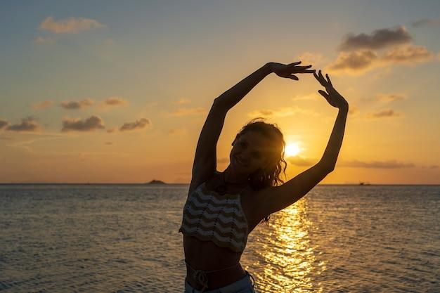 Jonge schoonheid meisje dansen op tropisch strand in de buurt van zeewater op paradijseiland bij zonsondergang, close-up. zomer concept. vakantie reizen.
