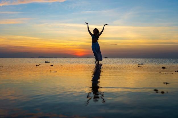 Jonge schoonheid meisje dansen op tropisch strand op zeewater op paradijseiland bij zonsondergang, close-up. zomer concept. vakantie reizen.