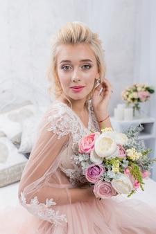 Jonge schoonheid mode bruid in winter decor met boeket bloemen in haar handen. mooie bruid portret bruiloft make-up en kapsel.