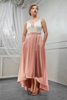 Jonge schoonheid, mooie vrouw in lange perzik jurk, hand op heup, loo