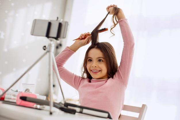 Jonge schoonheidsblogger. vrolijk pre-tienermeisje aan de tafel zitten en een haarlok borstelen terwijl ze zichzelf opneemt voor een blogbericht over schoonheid