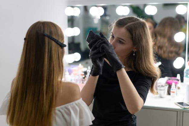 Jonge schoonheidsspecialiste blanke meisje houdt model wenkbrauw correctie schoonheidsspecialiste op het werk is de werkplek van een wenkbrauw specialist. sluitingsresultaat op telefoon maak een foto schoonheidsindustrie. levensstijl