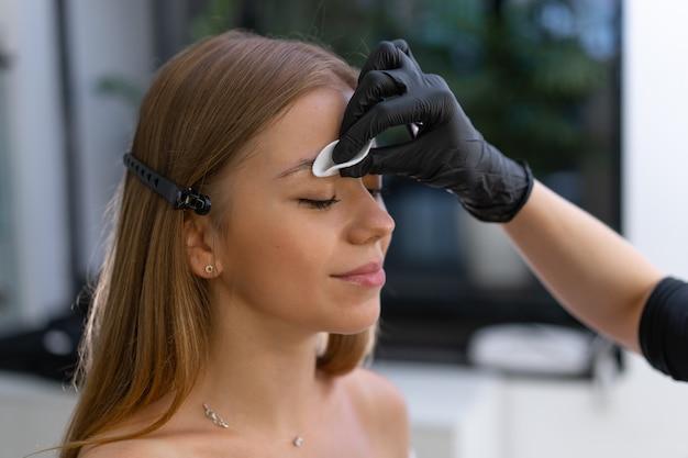 Jonge schoonheidsspecialiste blanke meisje houdt model wenkbrauw correctie schoonheidsspecialiste op het werk is de werkplek van een wenkbrauw specialist. wenkbrauwcorrectie en verfprocedure. schoonheidsindustrie. levensstijl