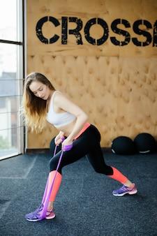 Jonge schoonheidsvrouw die oefening met riemen van elastieken in gymnastiek doet